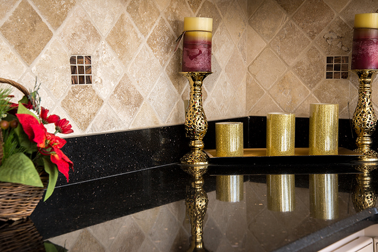 Black Galaxy granite kitchen countertops accented with Classic Travertine tile backsplash
