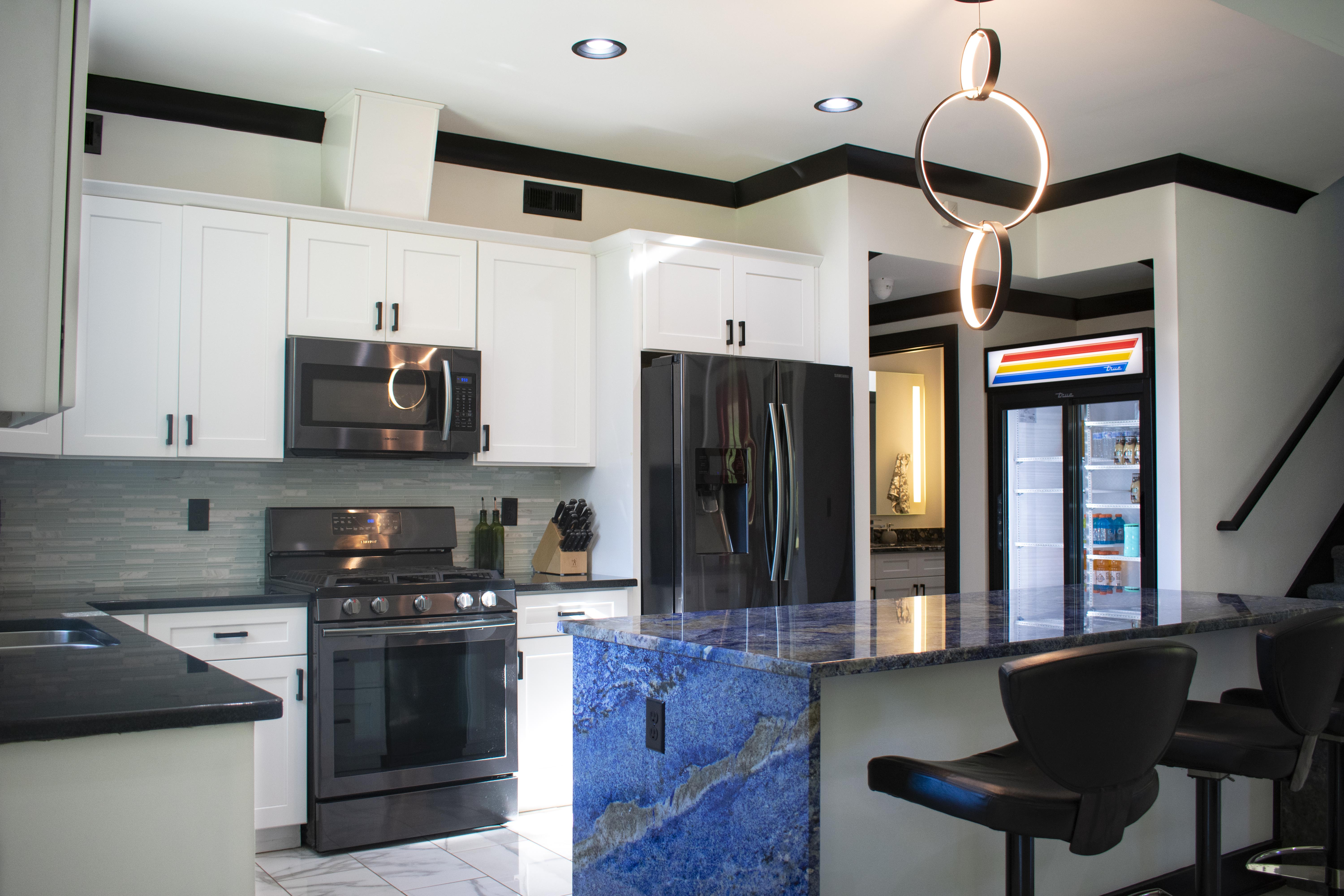 Blue Bahia granite countertops kitchen island with waterfall edges paired with white shaker cabinets and stacked tile backsplash