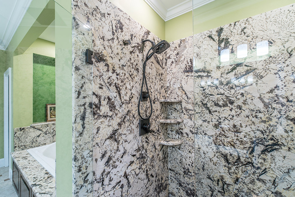 Beautiful Delicatus White granite used for the walls in the walk-in shower and the surrounds for the garden tub adding visual appeal