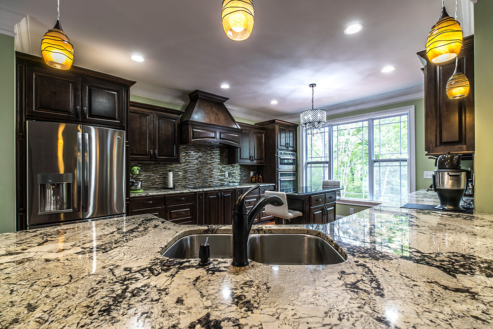 Spacious kitchen with large islands topped with Delicatus White granite countertops