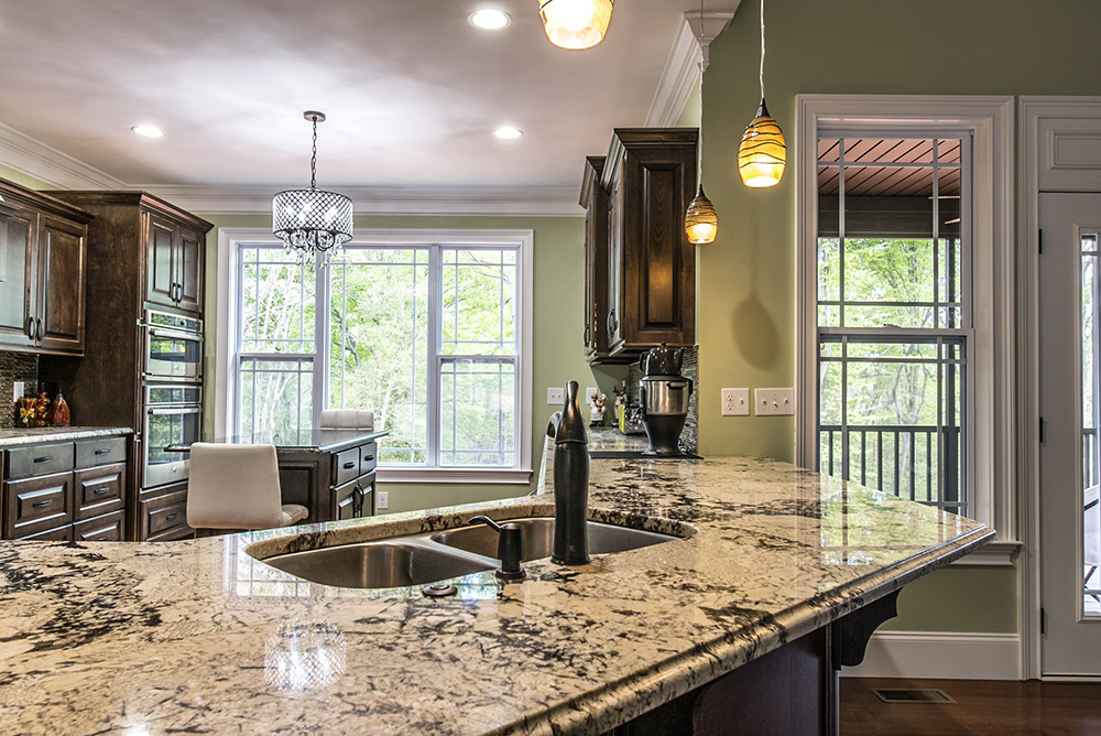 Delicatus White granite kitchen island with undermount double bowl sink and oil rubbed bronze faucet