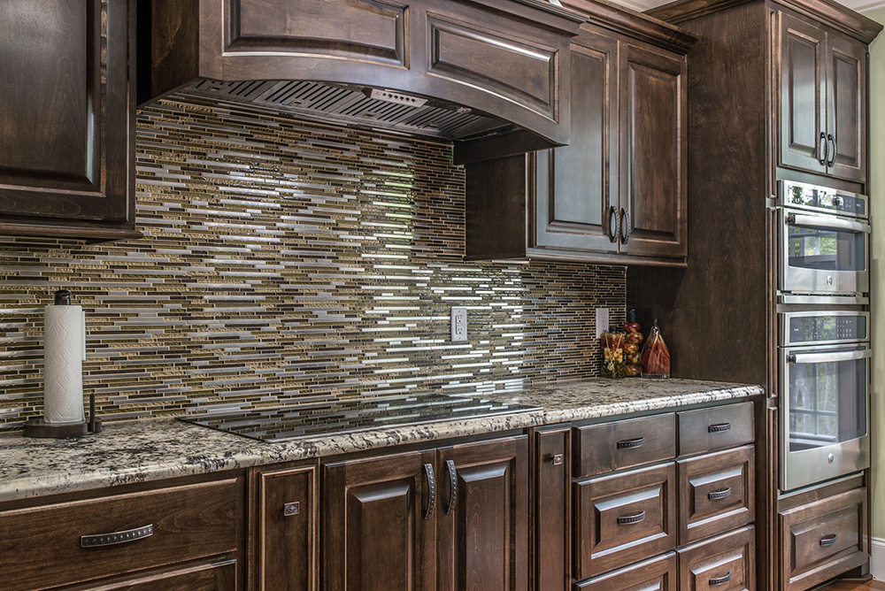 Delicatus White granite chef's area with earthy tone and stainless tile backsplash ample storage in beautiful dark brown cabinetry