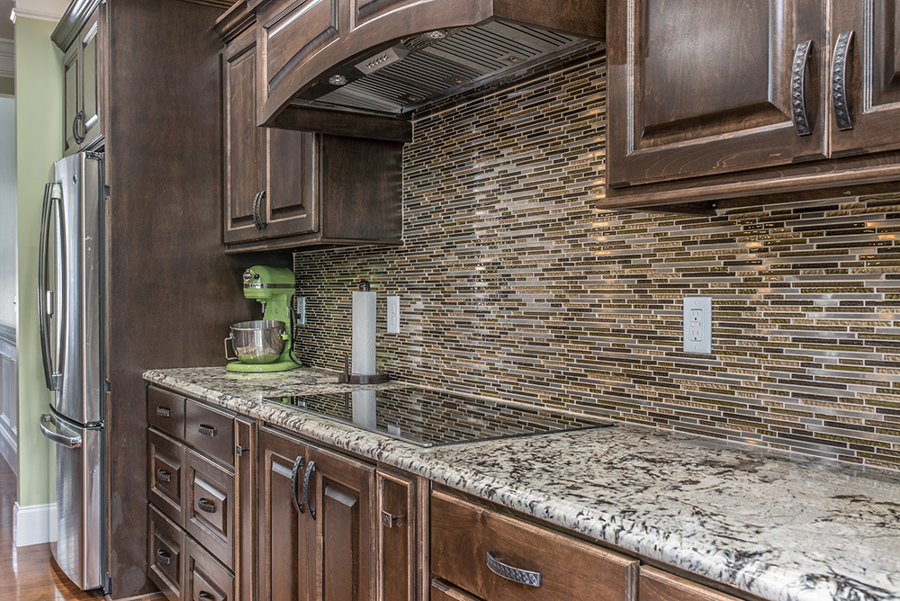 Delicatus White granite with flush cooktop stacked glass tile backsplash and dark brown cabinets