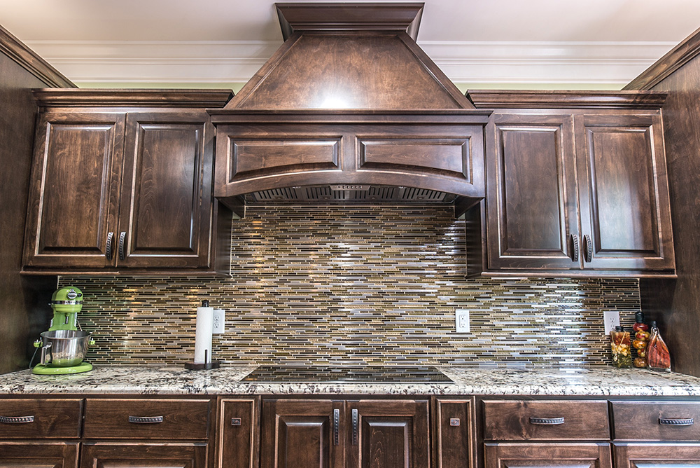 Delicatus White granite countertop with glass tile backsplash and dark brown cabinets