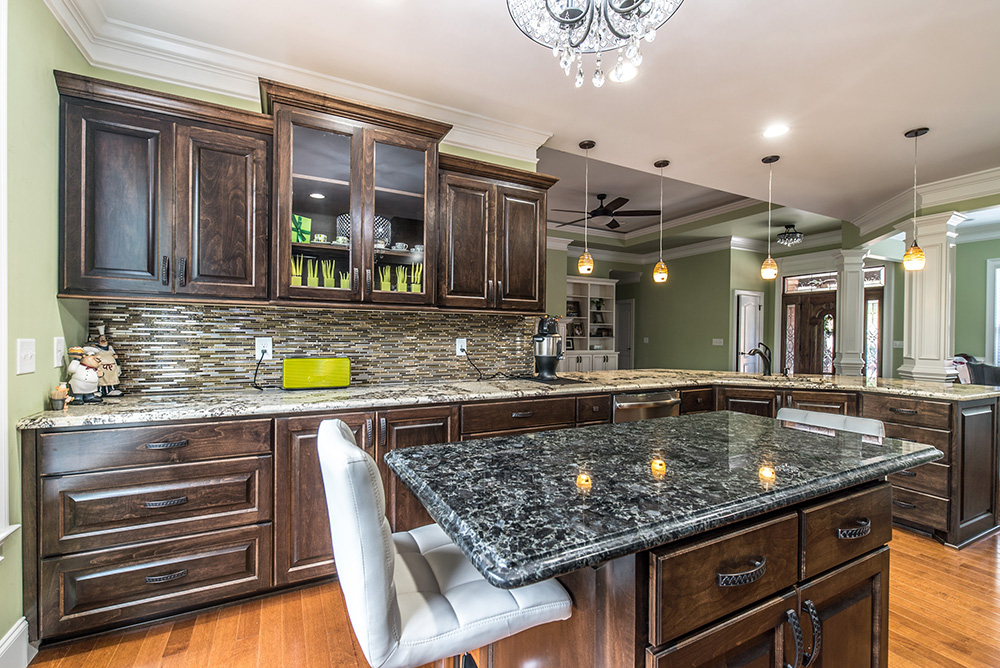 Delicatus White granite kitchen countertops contrasted with a Blue Eyes granite Island.