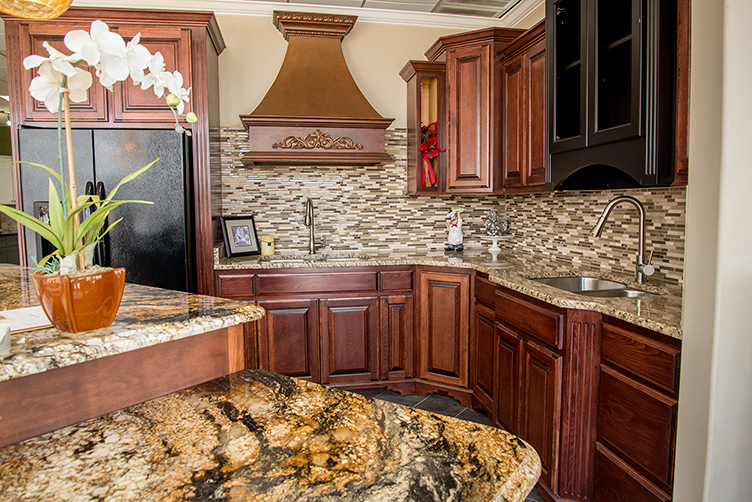 Kitchen island with Golden Crystal granite paired with Stone Radiance tile backsplash, Ornamental granite countertops and Saddle Brown cabinets