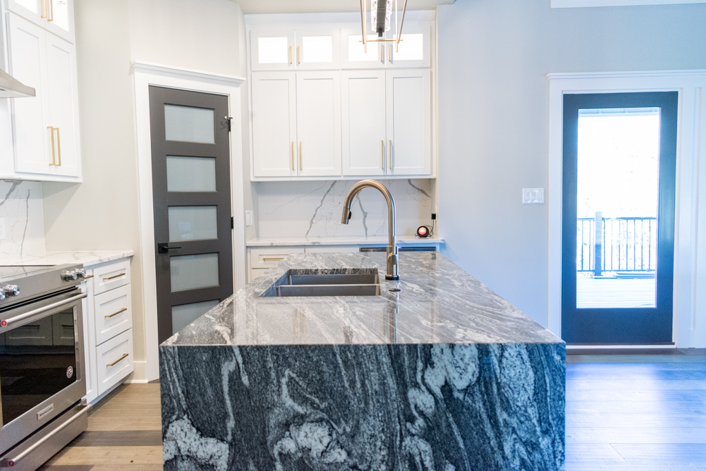 Spacious kitchen island topped with Juperana Granite featuring waterfall edges
