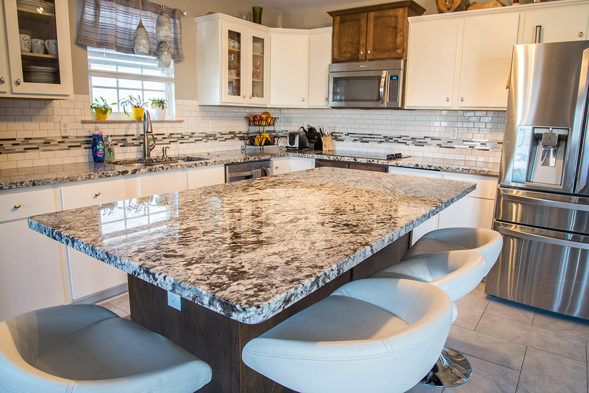 Large kitchen island counter made of Lennco Granite.
