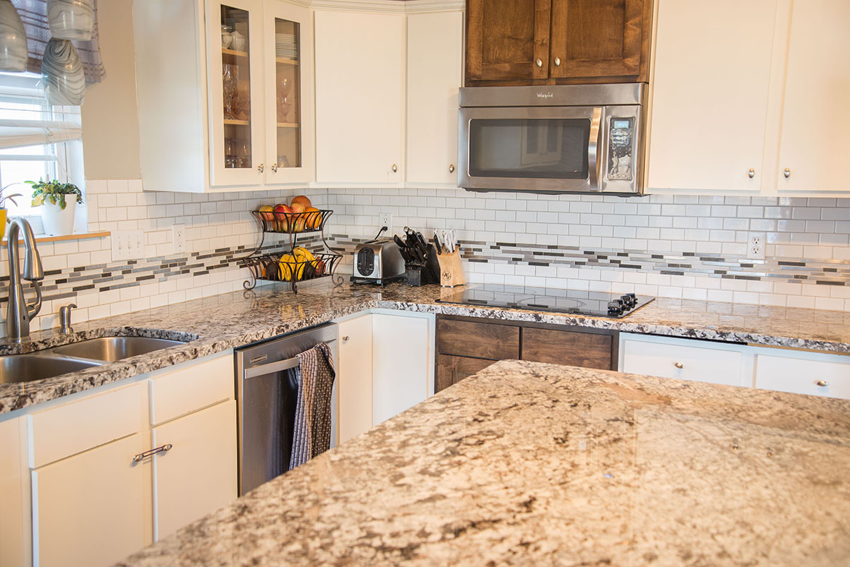 Large kitchen island counter made of Lennco Granite. Subway and Glass tile bring the room together