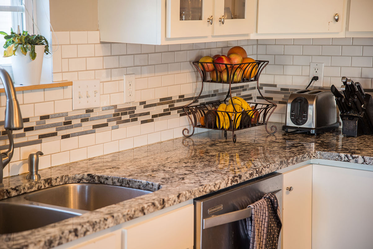 Lennco Granite kitchen countertops with subway and glass tile backsplash