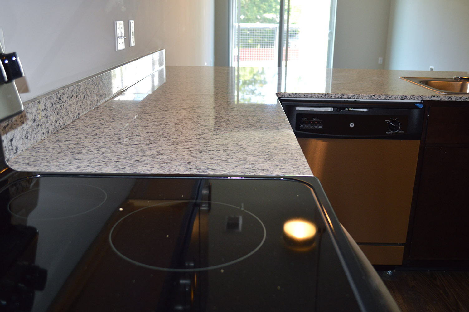 Using granite countertops in the kitchens Main & Stone effectively moves the eyes from room to room with their open concept floor plans