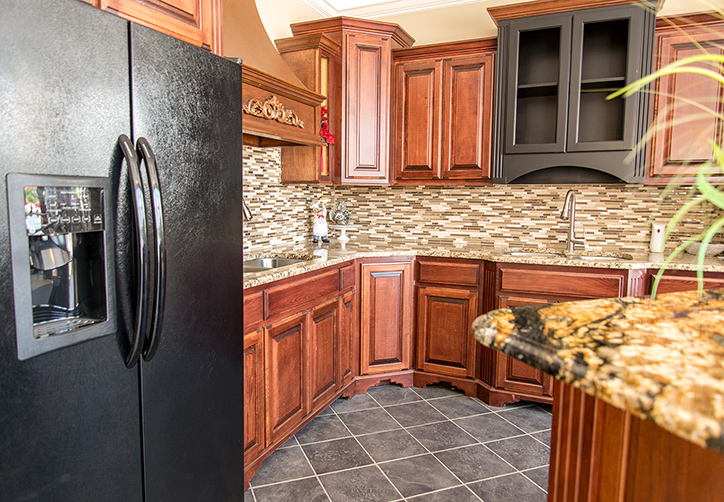 Ornamental granite countertops matched with Gold Crystal granite island top, Stone Radiance tile backsplash and Saddle Brown cabinets
