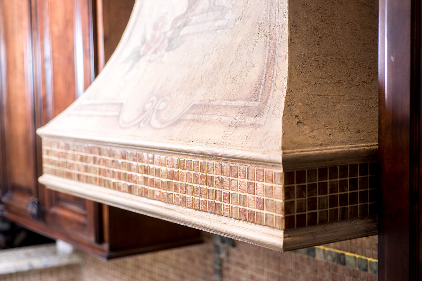 Gorgeous range hood with small square earthy toned tile border