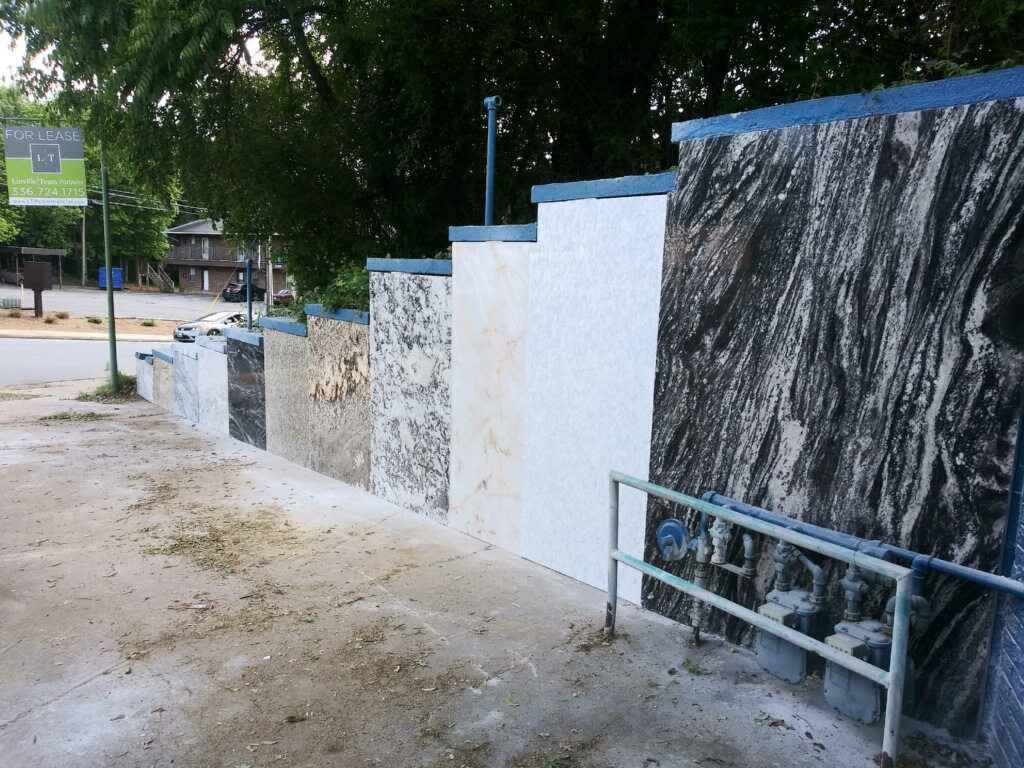 Using the existing architecture, we placed a portion of our outdoor slab showroom on an existing retaining wall.