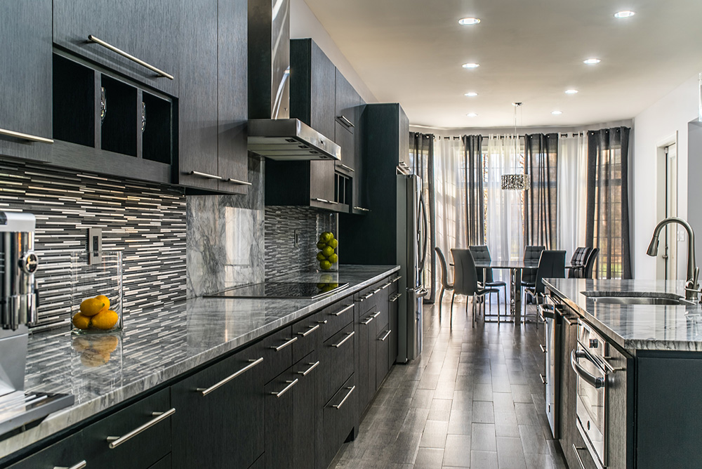 Modern kitchen with tile backsplash and dark cabinets topped with Super White marble countertops and stainless appliances