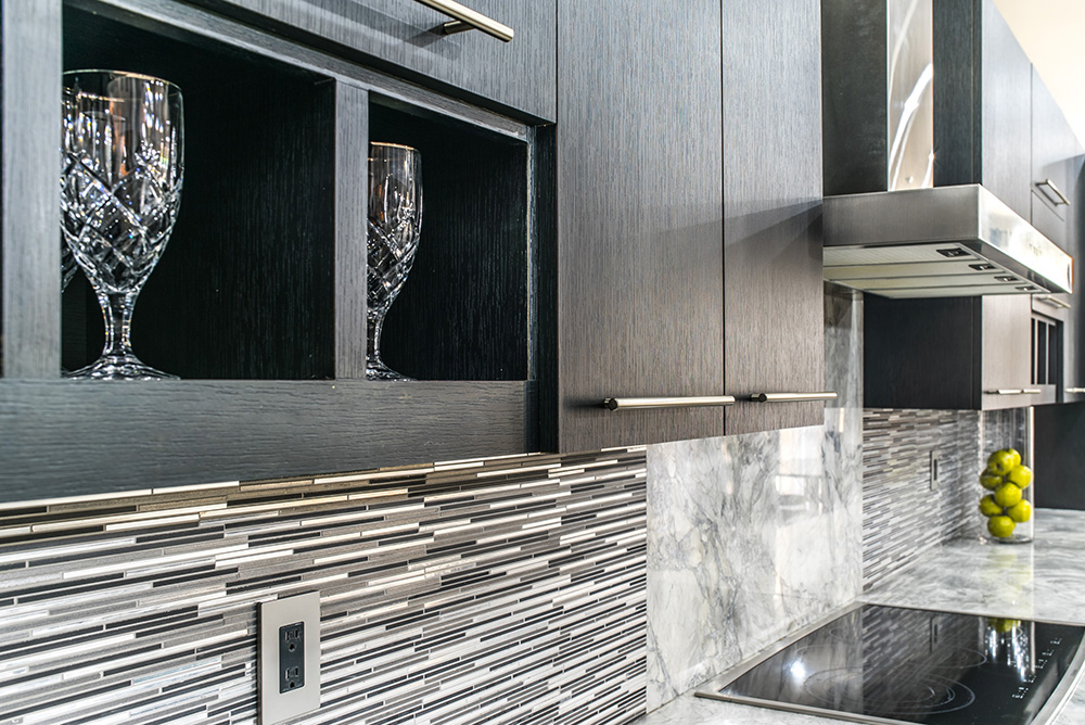 Dark wood cabinets contrasted by Super White marble wall accent and tile backsplash