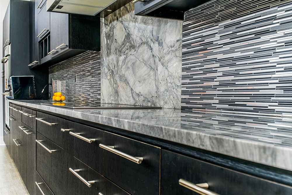 Super White marble countertops atop dark wood cabinets accented with tile backsplash