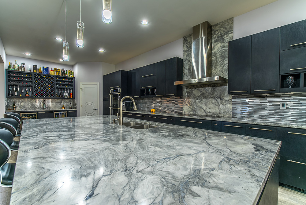 Large Super White marble kitchen island with seating for guests, undermount sink and space for food prep