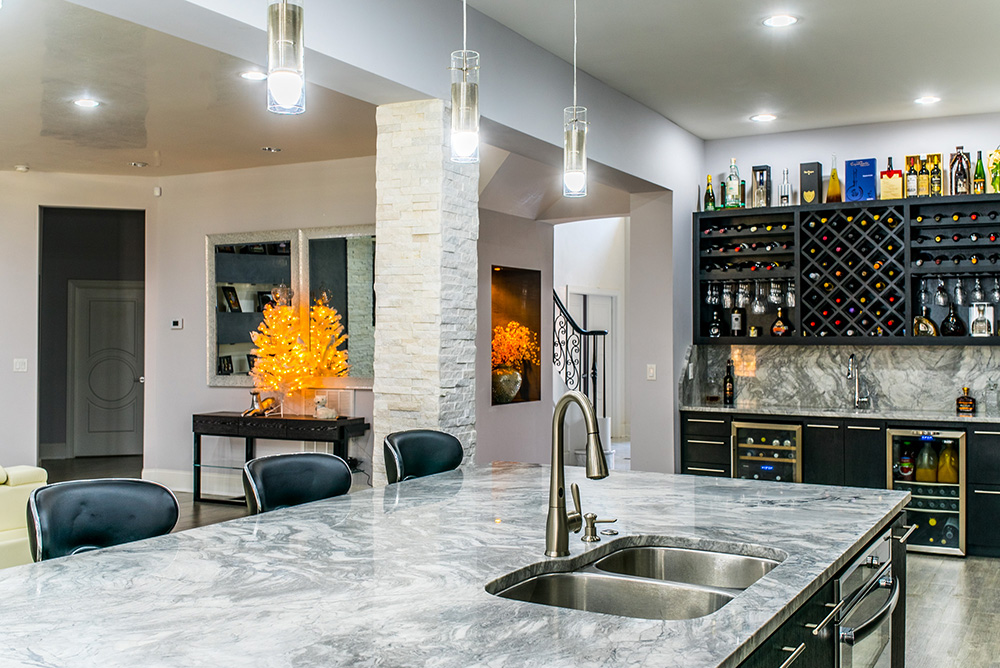 Large kitchen island topped with Super White marble and double bowl stainless steel sink
